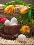 Ovos brancos na cesta marrom pequena com tulips Fotos de Stock Royalty Free