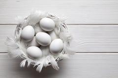 Ovos brancos na cesta no fundo de madeira branco das pranchas imagem de stock royalty free