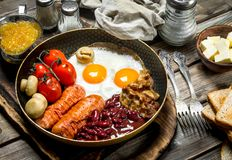 Ovos breakfastFried ingleses com salsichas, bacon e os feijões enlatados vermelhos imagem de stock