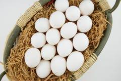 Ovos colocados no feno na cesta Fotografia de Stock Royalty Free
