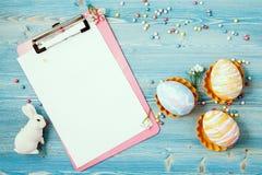 Ovos coloridos da Páscoa em um fundo de madeira azul com uma tabuleta, o coelho e um fundo do caderno para um cartão, concep da P Imagem de Stock Royalty Free