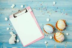 Ovos coloridos da Páscoa em um fundo de madeira azul com uma tabuleta, o coelho e um fundo do caderno para um cartão, concep da P Imagem de Stock