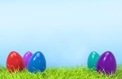 Ovos coloridos da Páscoa na grama verde e no fundo azul Fotografia de Stock Royalty Free