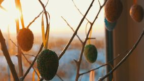 Ovos coloridos da Páscoa nos ramos decorativos brancos Um ramalhete à moda de suportes de ovos da páscoa na soleira no video estoque
