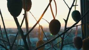 Ovos coloridos da Páscoa nos ramos decorativos brancos Um ramalhete à moda de suportes de ovos da páscoa na soleira nos raios filme