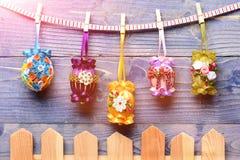 Ovos coloridos decorados com linha, grânulos da Páscoa que penduram no pregador de roupa Imagem de Stock