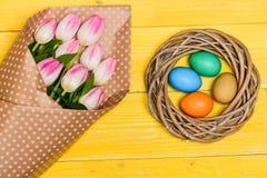 Ovos coloridos e flores frescas da tulipa do ramalhete na opinião superior do fundo amarelo Feriado da mola A tradição comemora e imagens de stock royalty free