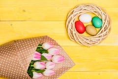 Ovos coloridos e flores frescas da tulipa do ramalhete na opinião superior do fundo amarelo A tradição comemora easter Feriado da imagem de stock