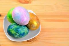Ovos coloridos em uma placa em um fundo de madeira natural Fotos de Stock Royalty Free
