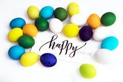 Ovos coloridos festivos da Páscoa em um fundo branco com um ` feliz de easter do ` da caligrafia do cartão ovos amarelo, azul, ve foto de stock royalty free