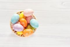 Ovos coloridos na cesta em um fundo branco Imagens de Stock