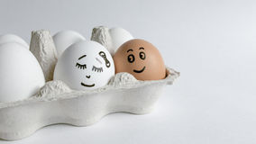Ovos com as caras engraçadas no pacote em um fundo branco Foto do conceito da Páscoa Caras nos ovos fotografia de stock