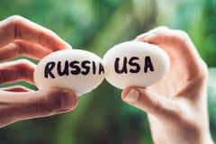 Ovos com as inscrição de Rússia e do Estados Unidos, luta, que são quebradas conflito entre EUA contra Rússia foto de stock royalty free