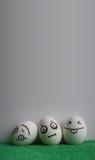 Ovos com a foto das caras para seu projeto fotografia de stock