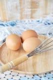 Ovos com o batedor de ovos na placa de madeira Imagens de Stock Royalty Free