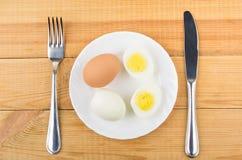 Ovos completos e metade dos ovos na placa branca, forquilha Imagem de Stock Royalty Free