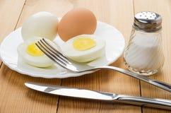 Ovos completos fervidos e metade dos ovos na placa branca Fotografia de Stock