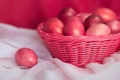 Ovos cor-de-rosa da Páscoa na cesta Imagem de Stock