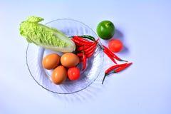 Ovos, couve, pimentão, limão verde e tomate no prato de vidro Foto de Stock Royalty Free