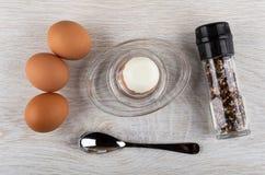 Ovos cozidos, ovo descascado no suporte de ovo, colher, frasco com o condimento na tabela de madeira Vista superior fotografia de stock
