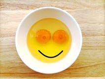 Ovos crus da cara feliz do sorriso na bacia no fundo de madeira da tabela imagens de stock