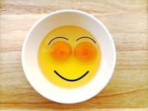 Ovos crus da cara feliz do sorriso na bacia no fundo de madeira da tabela foto de stock