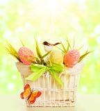 Ovos da cesta da Páscoa, objetos da mola decorados pelo montículo do pássaro da grama Fotografia de Stock Royalty Free