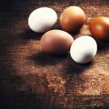 Ovos da exploração agrícola em um fundo rústico de madeira Marrom e branco frescos Imagens de Stock