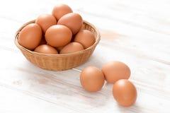 Ovos da galinha de Brown na cesta e na superfície de madeira Foto de Stock
