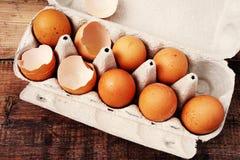 Ovos da galinha e shell de ovos quebrados em uma bandeja do cartão Foto de Stock Royalty Free