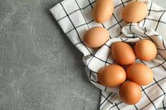 Ovos da galinha na toalha de cozinha no fundo cinzento fotos de stock royalty free