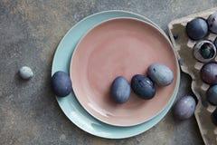 Ovos da páscoa azuis e violetas em uma placa cerâmica em uma cor de viver Coral Pantone em um fundo de pedra cinzento, espaço da  fotografia de stock