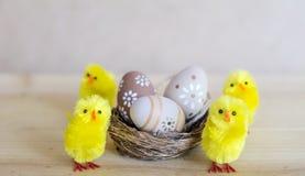 Ovos da páscoa bege no ninho pequeno com galinhas Imagem de Stock