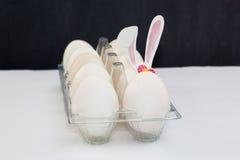 Ovos da páscoa brancos na bandeja na tabela branca Imagens de Stock