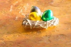 Ovos da páscoa brilhantes, coloridos dentro no amarelo Fundo, ovos da páscoa coloridos Ovos da páscoa da árvore no ninho branco Foto de Stock