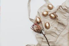 Ovos da páscoa colocados lisos mínimos do ouro com a flor de linho do avental e do protea no fundo branco imagem de stock