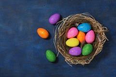 Ovos da páscoa coloridos brilhantes em um ninho em um fundo azul Vista superior, configuração lisa, lugar para o texto imagens de stock