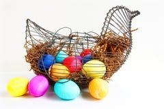 Ovos da páscoa coloridos brilhantes em uma cesta da galinha do fio Fotografia de Stock