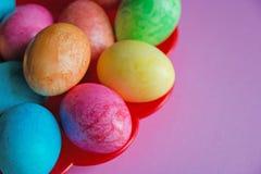 Ovos da páscoa coloridos brilhantes na placa vermelha no fundo cor-de-rosa Fotografia de Stock Royalty Free