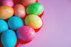 Ovos da páscoa coloridos brilhantes na placa vermelha no fundo cor-de-rosa Imagens de Stock Royalty Free