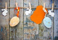 Ovos da páscoa coloridos, coelhinhos da Páscoa e cartão vazio pendurando em r Imagem de Stock Royalty Free