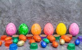 Ovos da páscoa coloridos com ovos da páscoa do chocolate e carne doce na frente do fundo cinzento Fotos de Stock