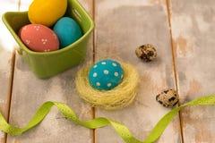 Ovos da páscoa coloridos do close-up em uma caixa e em um ninho verdes, fitas em um fundo de madeira Estilo rústico Imagens de Stock