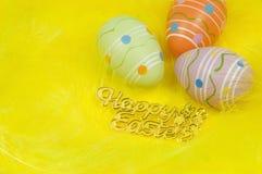 Ovos da páscoa coloridos e penas amarelas Imagem de Stock