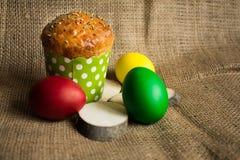 Ovos da páscoa coloridos e um bolo festivo, fundo rústico foto de stock