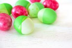 Ovos da páscoa coloridos em cores verdes e cor-de-rosa na aba de madeira branca Fotos de Stock Royalty Free