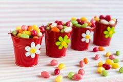 Ovos da páscoa coloridos em quatro cubetas vermelhas Fotografia de Stock