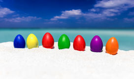 Ovos da páscoa coloridos em seguido em uma praia tropical Fotos de Stock