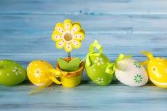 Ovos da páscoa coloridos em um suporte da linha e de nota da flor no fundo de madeira azul Fotografia de Stock