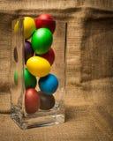 Ovos da páscoa coloridos em um vaso de vidro, fundo rústico fotos de stock royalty free